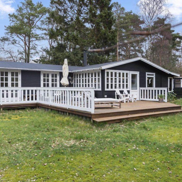 Zwart houten vakantiehuis in Denemarken, met witte kozijnen en houten veranda