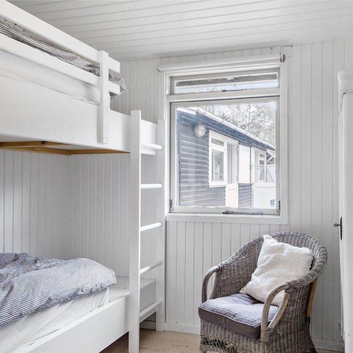 Een van de slaapkamers van het vakantiehuis met een wit stapelbed