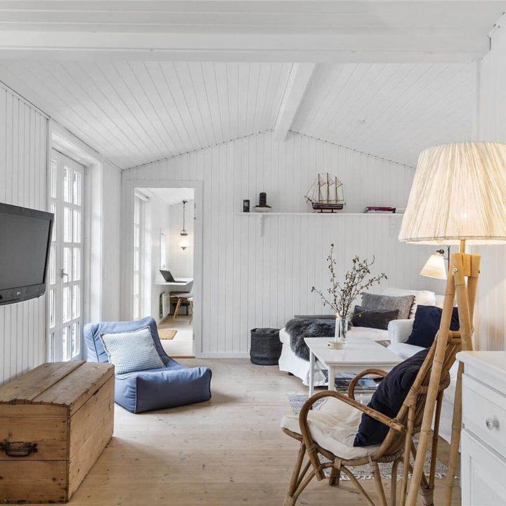 Zitkamer met rotan stoel, houten schemerlamp, grijze zitzak en witte fauteuil