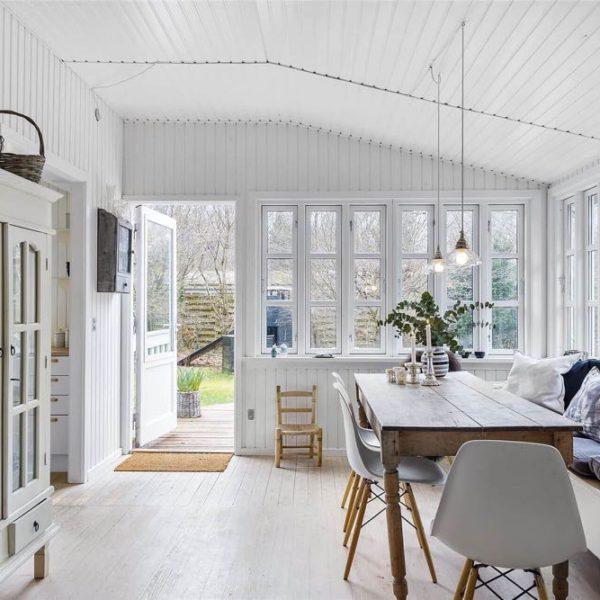 Wit houten interieur met houten tafel, witte kuipstoelen en brocante kast