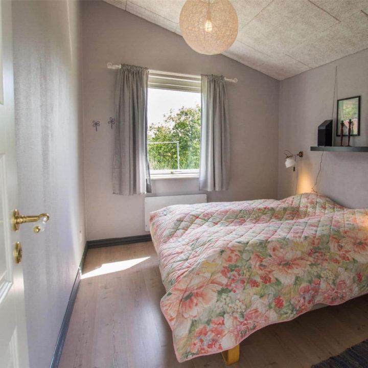 Een slaapkamer met een tweepersoons bed met bloemetjes sprei
