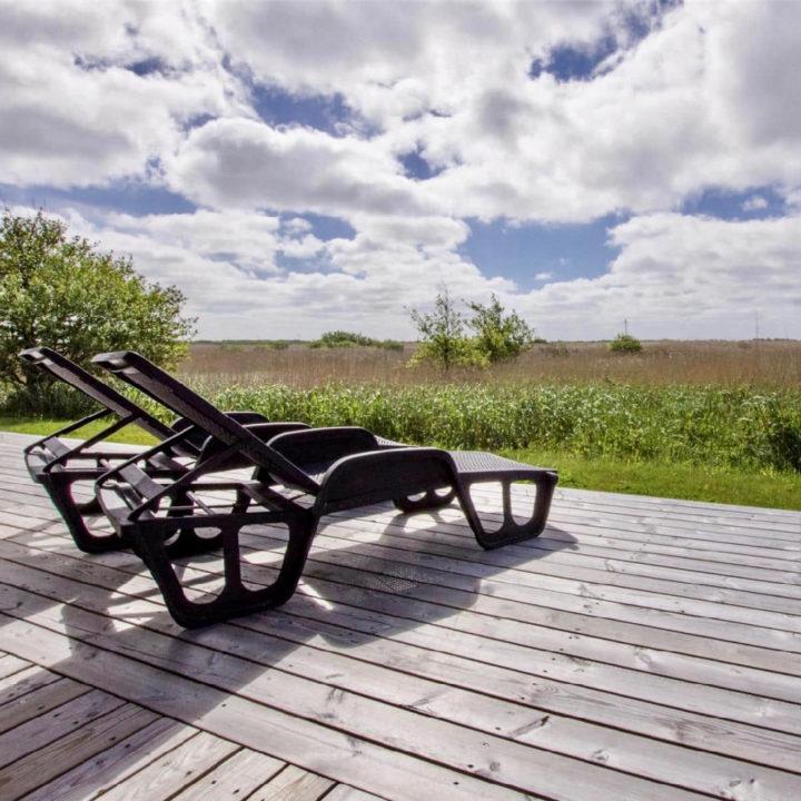 Rondom het vakantiehuis ligt een houten terras met meerdere zitjes. Ligbedden met uitzicht.