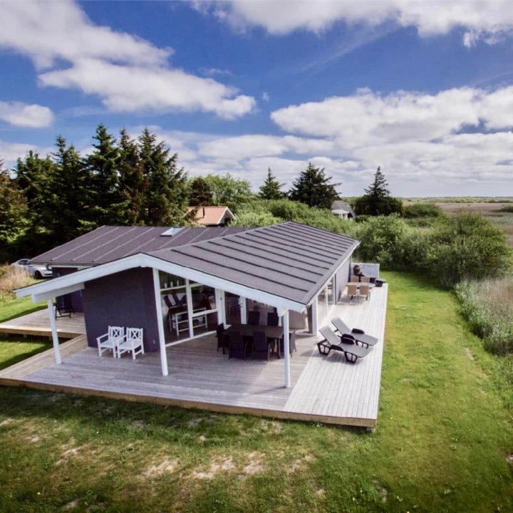 Deens vakantiehuis, grijs met wit, omringd door natuur