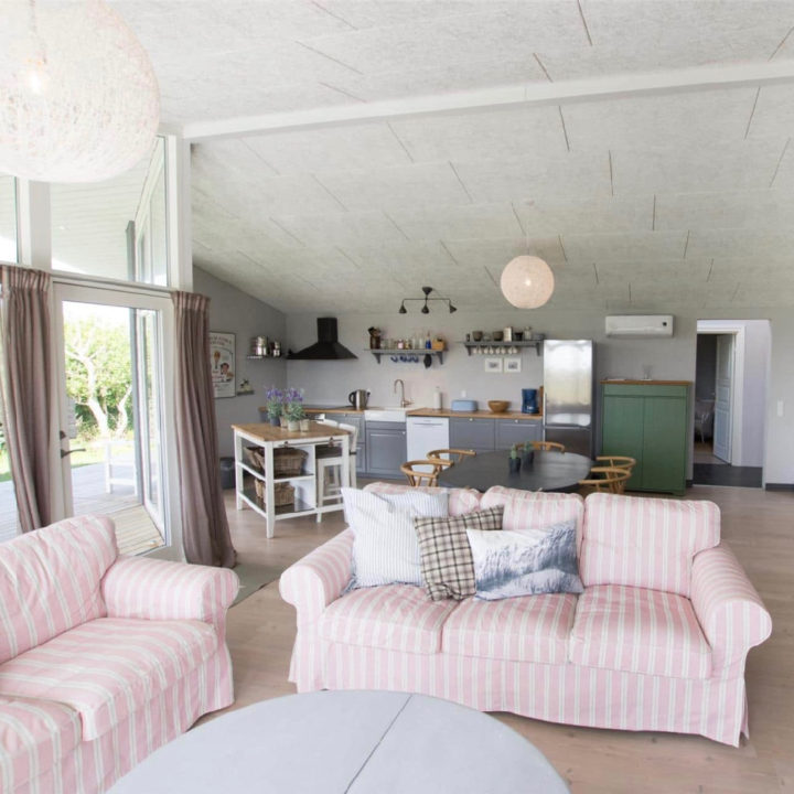 Woonkamer met roze banken, een landelijke keuken op de achtergrond