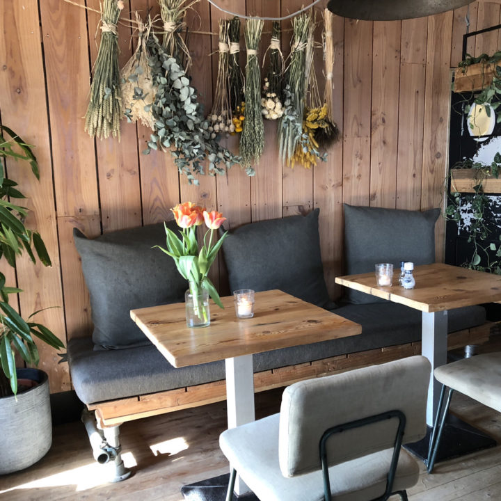 Bank met grijze kussens, gedroogde planten en bloemen aan de muur, twee tafeltjes met stoelen