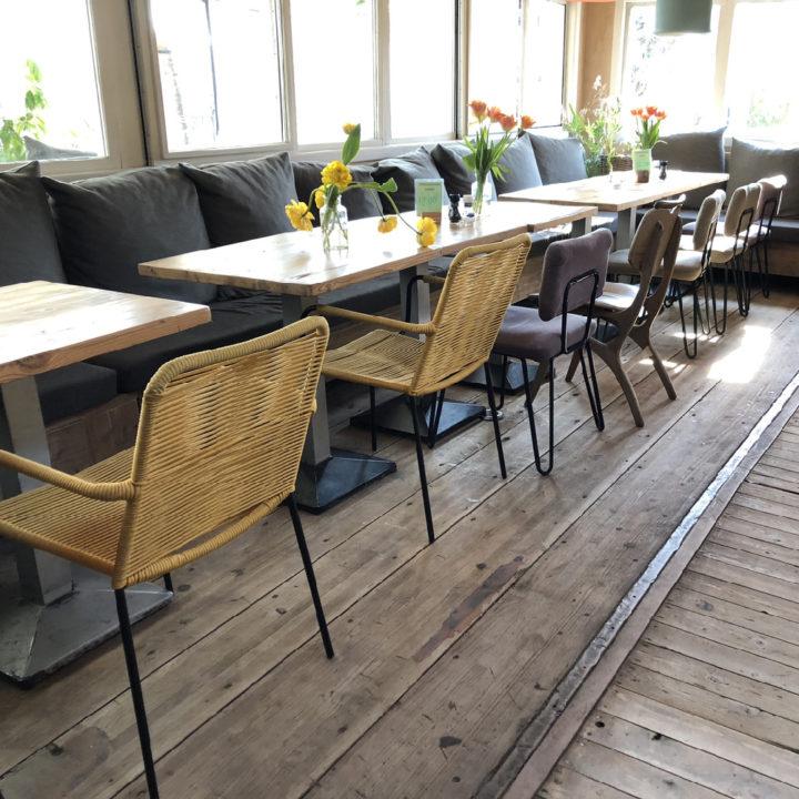 Lange rij tafels met een bank met kussens langs de ramen en verschillende stoelen
