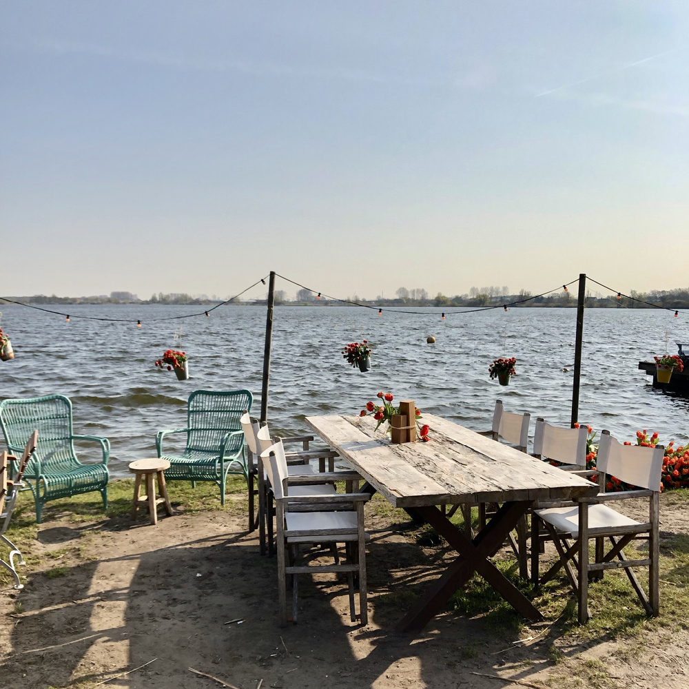 Een lange houten tafel met regisseur stoelen aan de rand van een meer bij Como & Co