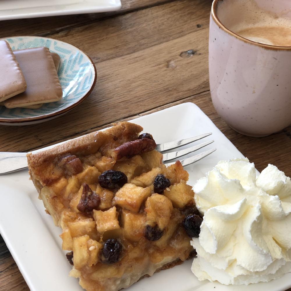 Appelplaattaart met kopje koffie en slagroom