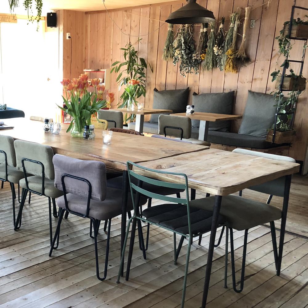Restaurant gedeelte van Como & Co met houten tafels en verschillende stoelen
