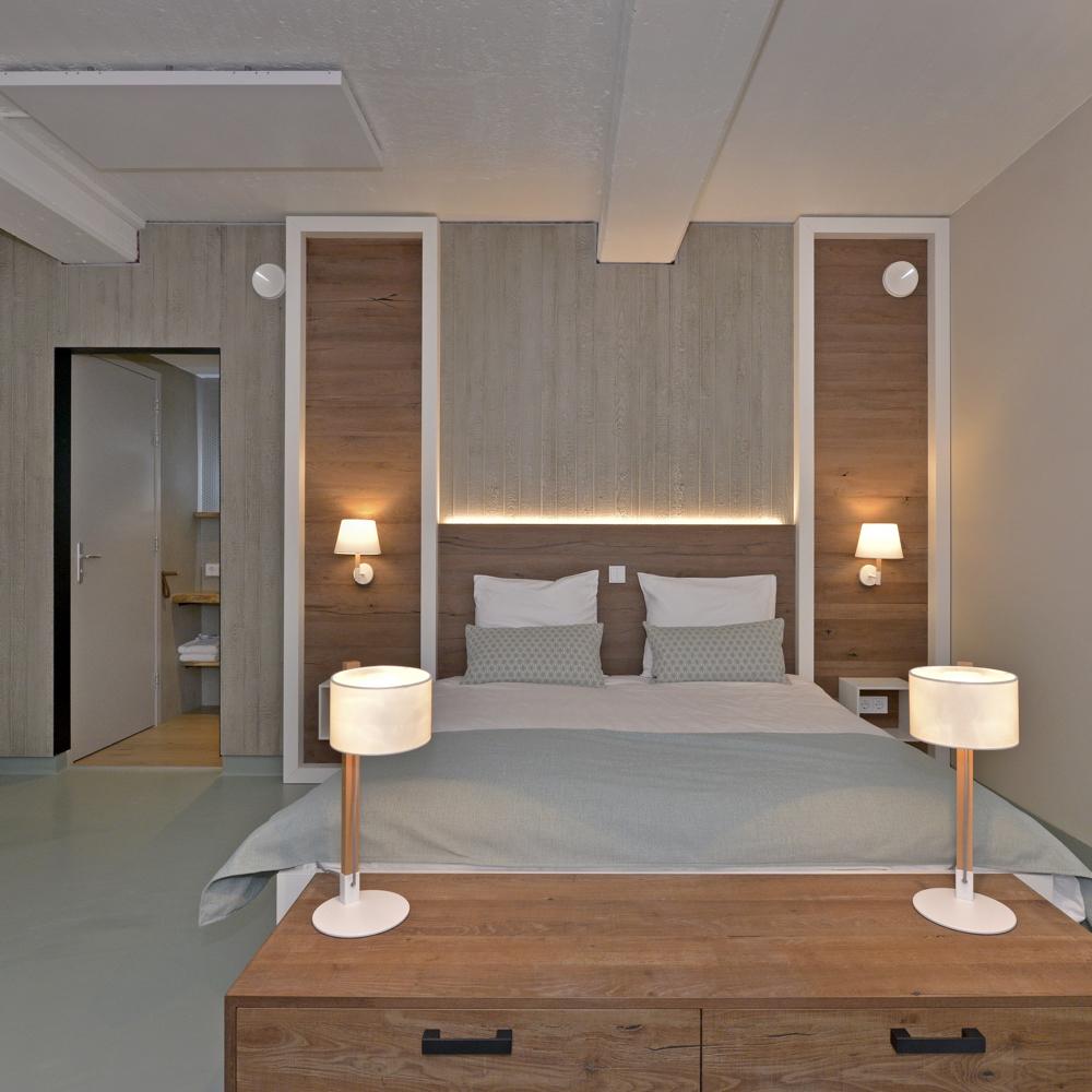 Opgemaakt tweepersoons bed met schemerlampjes, mintgroene sprei.