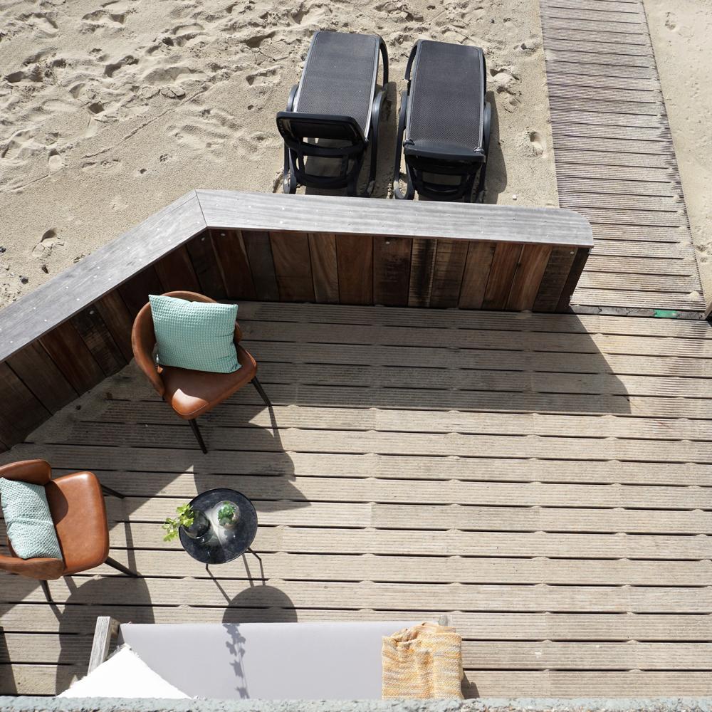 Terras met ligbedden, stoeltjes en een loungebank van bovenaf gezien.