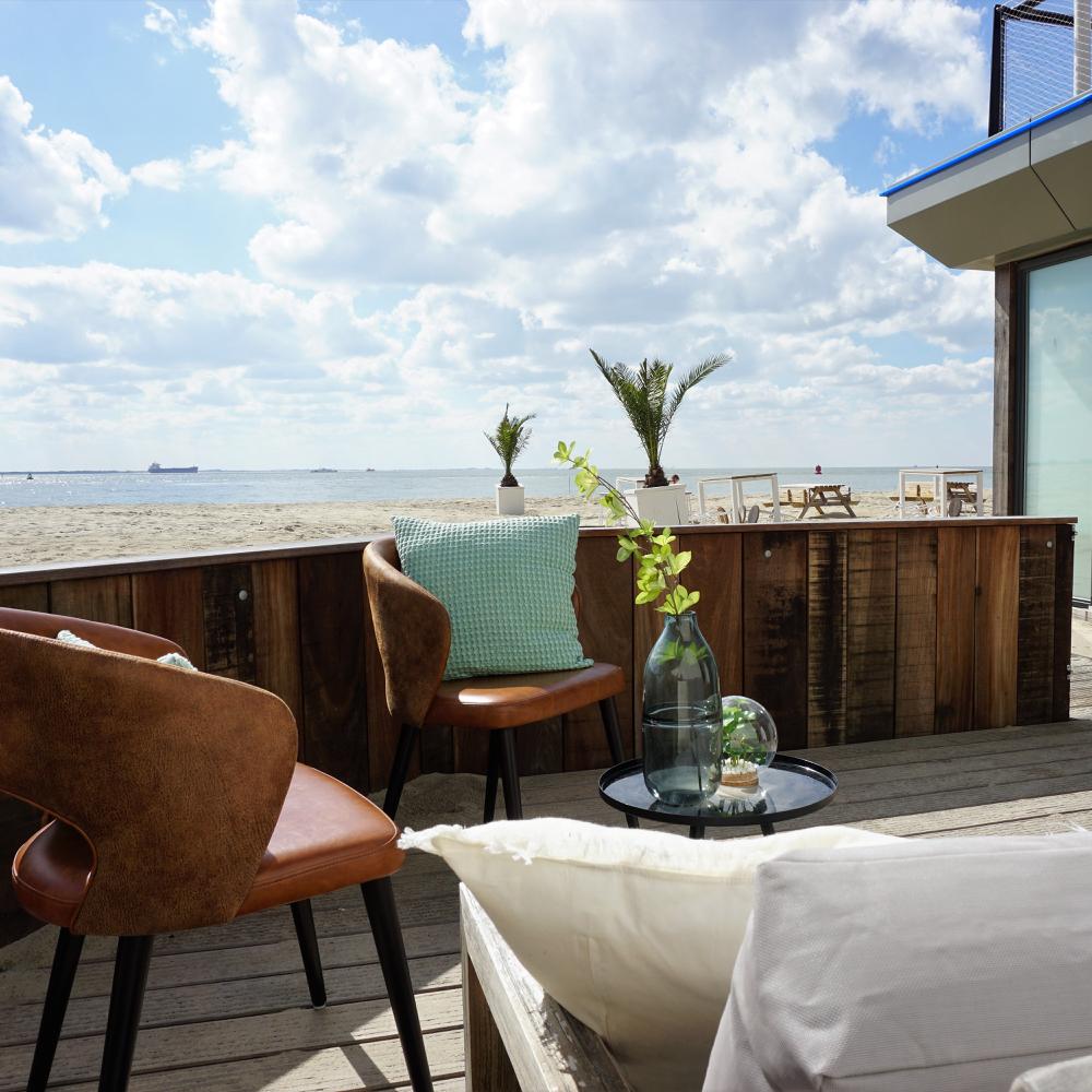 Privé terras met loungehoek en stoeltjes en zicht op zee