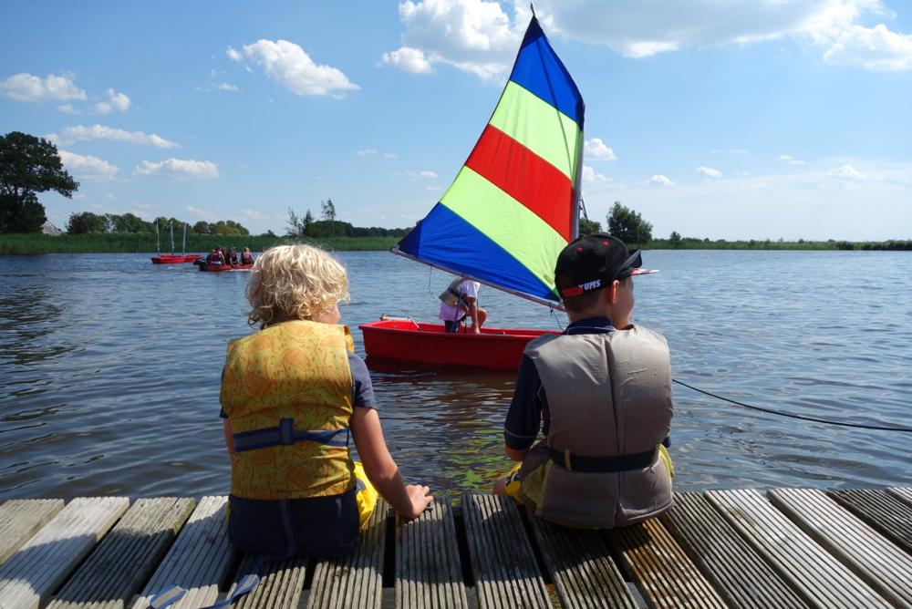 Twee jongetjes met zwemvest op een houten steiger, zeilbootje op de achtergrond