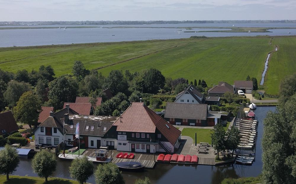 Luchtfoto van de boerderij waar de zeilschool gevestigd is