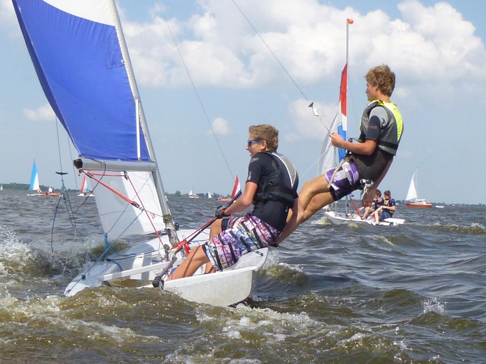 Twee tieners zeilen op een Fries meer, bij harde wind