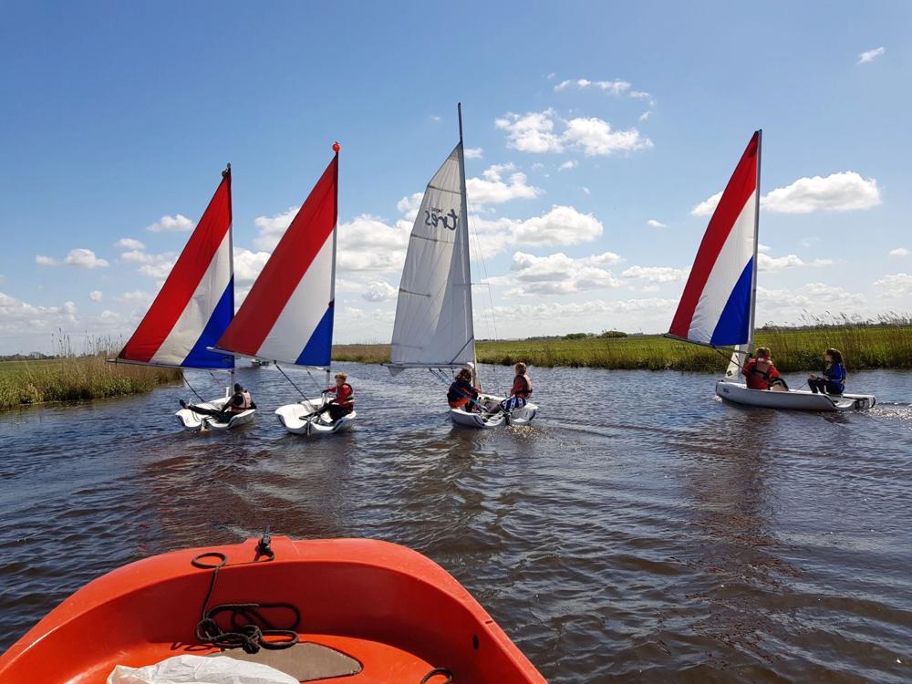 Vier zeilbootjes op een rij, met mooie wolkenlucht erachter