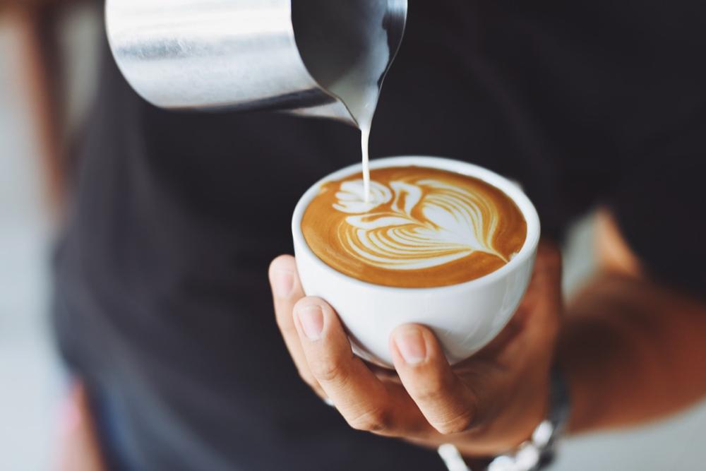 Een wit kopje waarin een cappuccino wordt geschonken