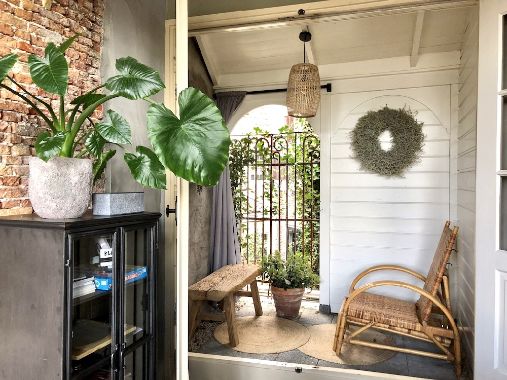 BInnenplaatsje in het vakantiehuisje met een rotan stoel, houten bankje en traliehek