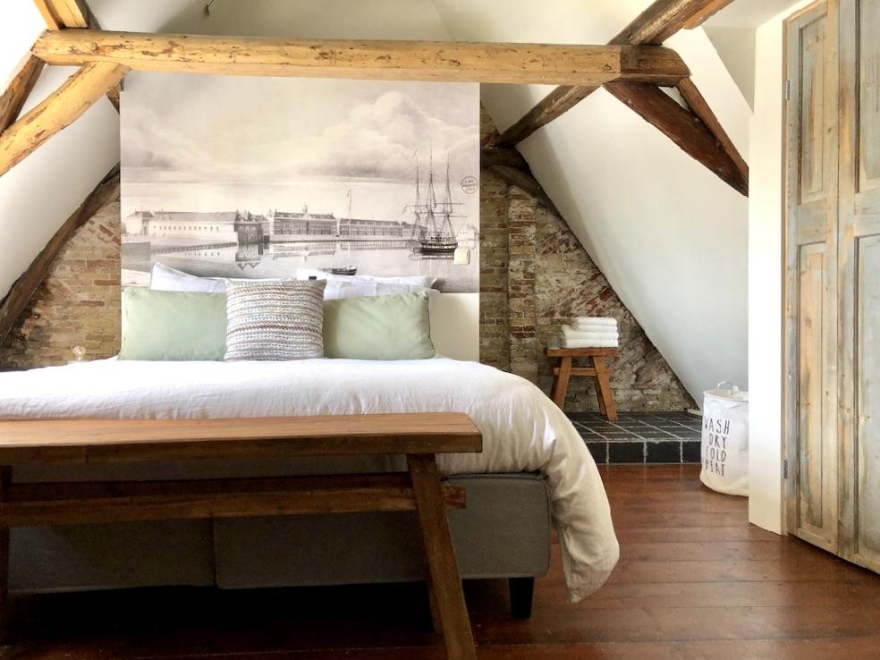Slaapkamer onder de balken met tweepersoonsbed met grote zwartwit foto op achtergrond