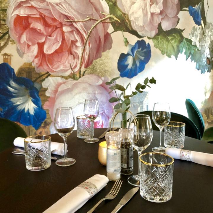 Gedekte tafel tegen een wand met bloemenbehang