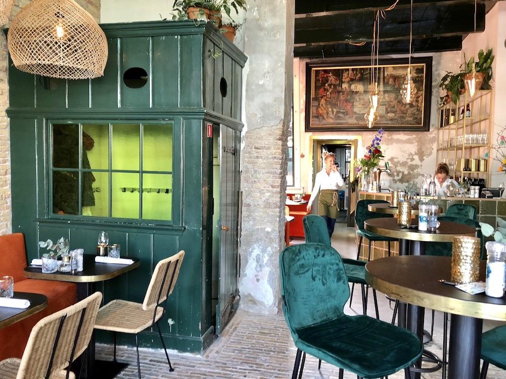 Eigentijds interieur met oranje banken, rieten stoelen, een groen houten garderobekast en robuuste muren