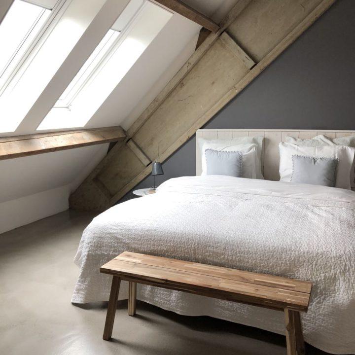 Luxe tweepersoons bed onder de stoere gebinten