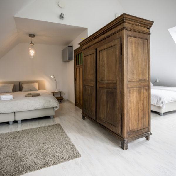 Slaapkamer met vier bedden, gescheiden door kasten