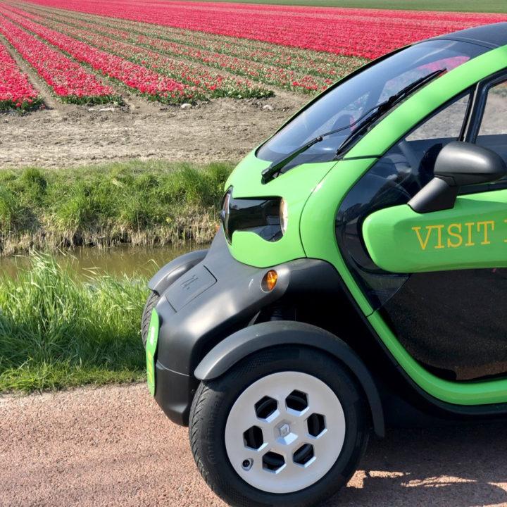 Groene Twizy met op de achtergrond rode tulpen
