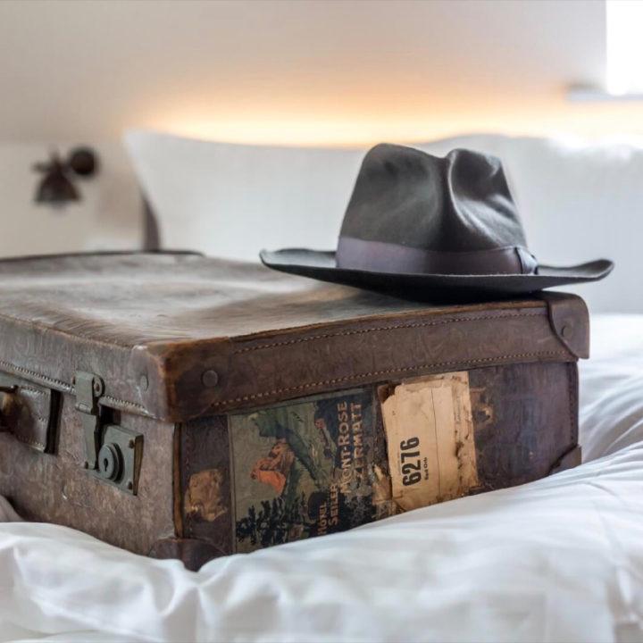Vintage koffer met hoed op een hotelbed