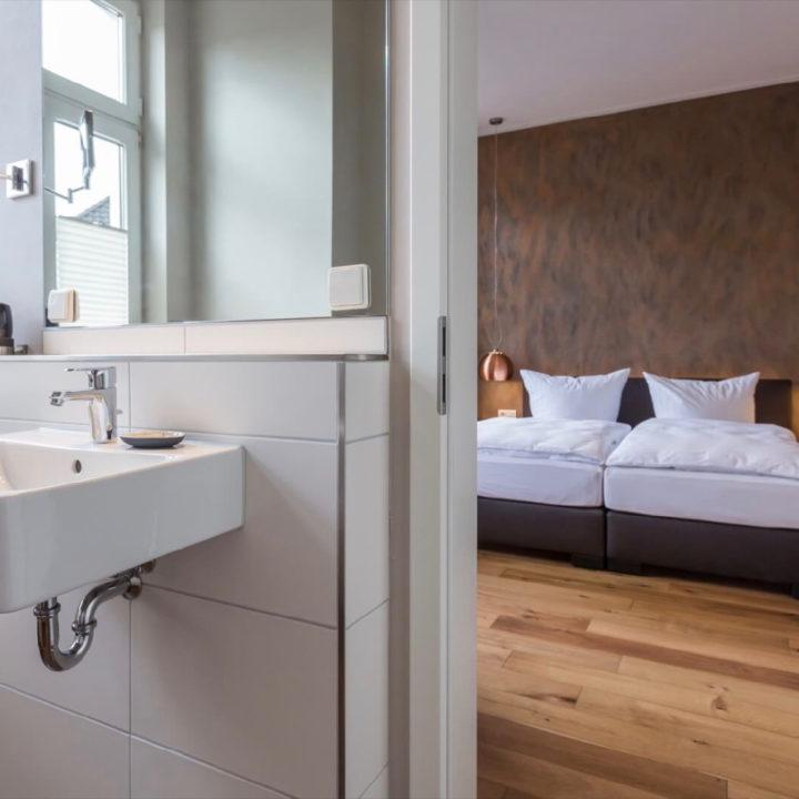 Doorkijkje vanaf een badkamer naar het bed in een hotelkamer