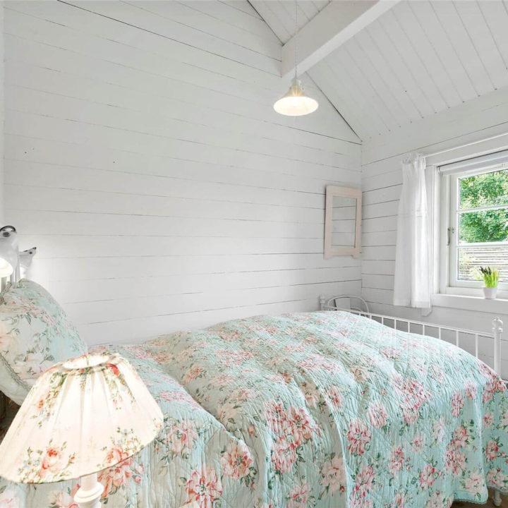 Romantische slaapkamer met spijlenbed, in een vakantiehuis in Denemarken