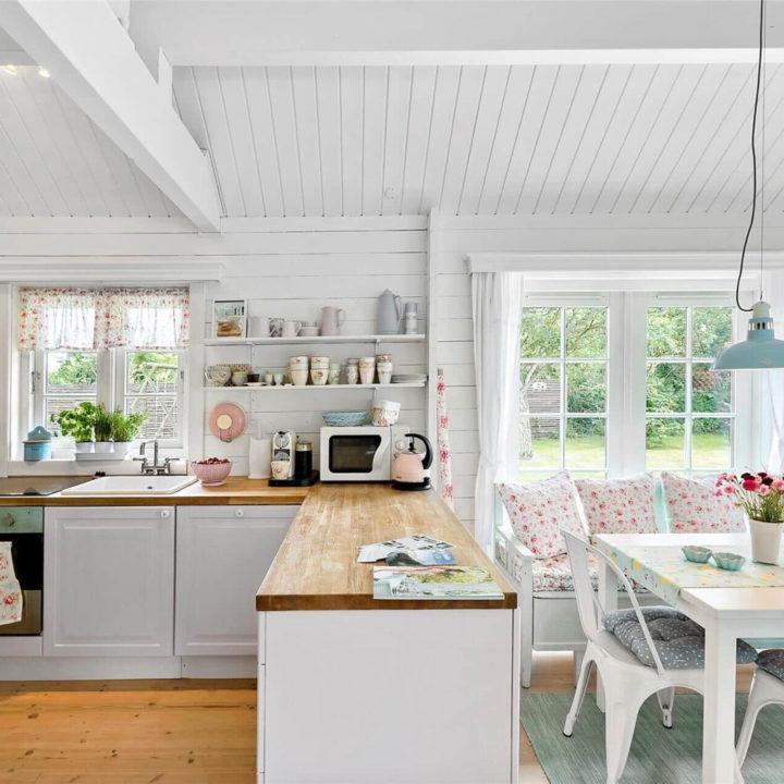 Witte keuken en eethoek met bloemetjes accessoires en kussens