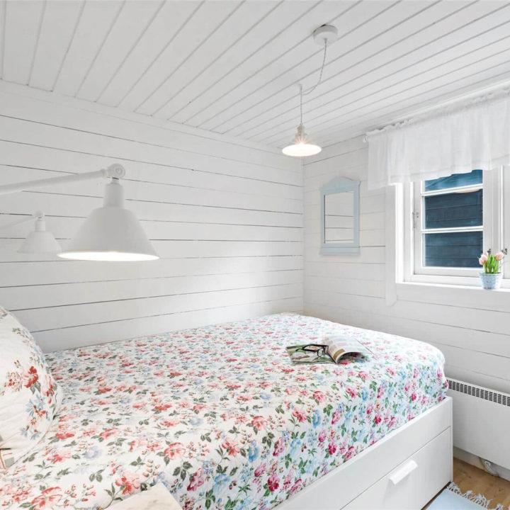 Witte houten slaapkamer met bloemetjes sprei op het bed