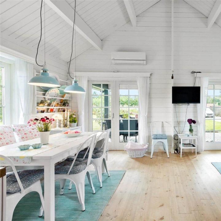 Witte houten eettafel met bloemetjes kussen in het vakantiehuis