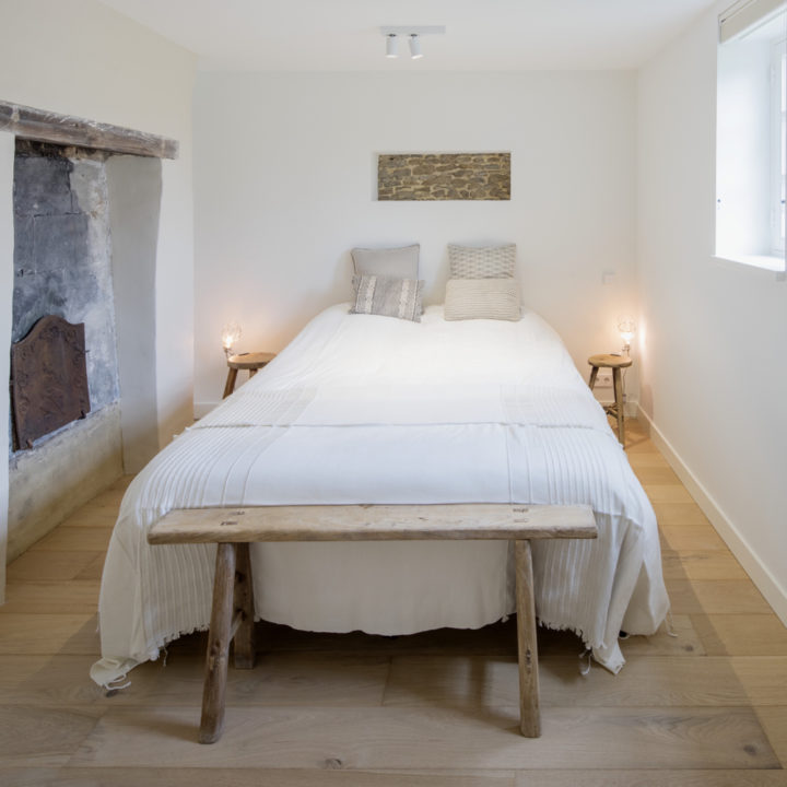 Tweepersoons bed met houten bankje in een vakantie appartement