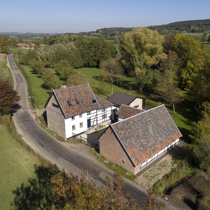 Vakwerkhoeve aan een landweggetje in de Limburgse heuvels