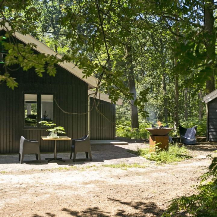 Zwart houten huis met vuurschaal en zitje