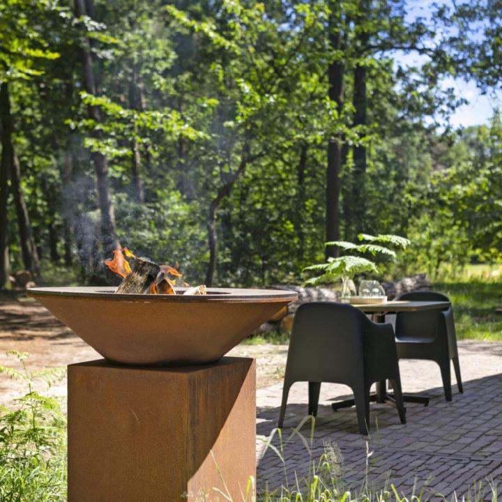 Brandende vuurschaal naast zwarte stoelen op het terras