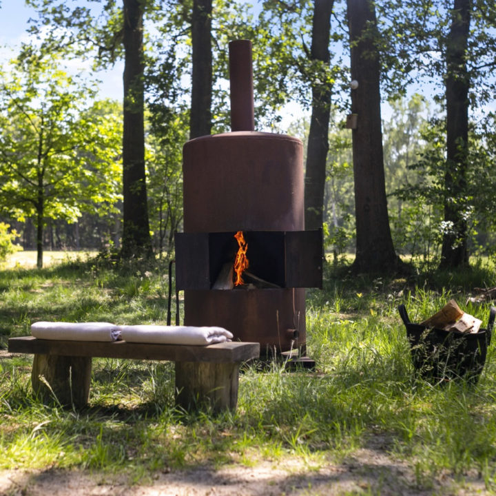 Brandende houtkachel in de tuin