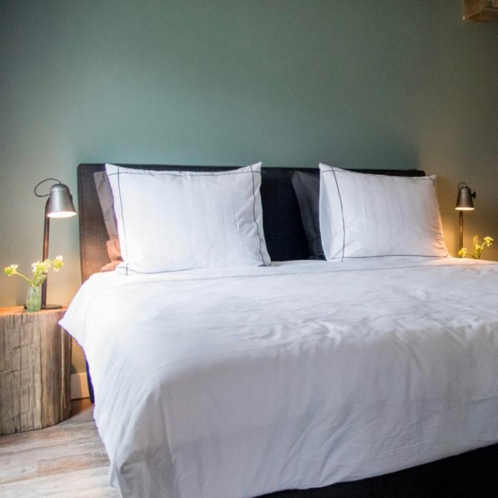 Opgemaakt tweepersoons bed met boomstronken als nachtkastjes
