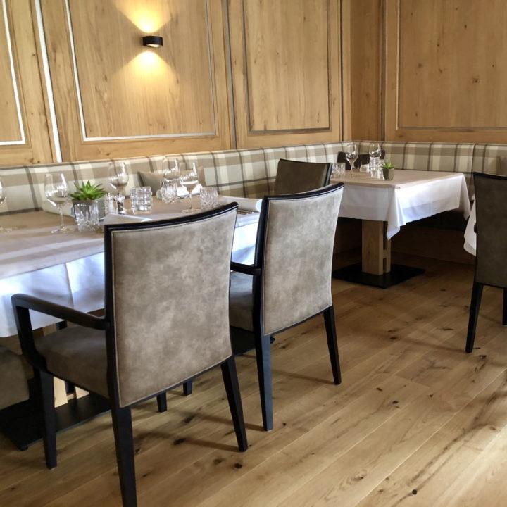 Gedekte tafels langs een houten wand met banken langs de muur