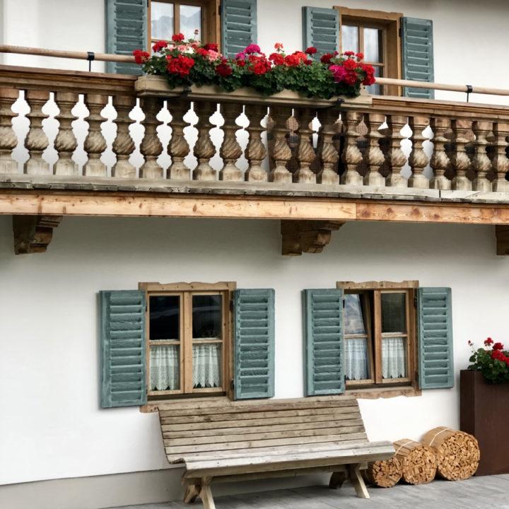 Groene luiken, geraniums en houten balkon