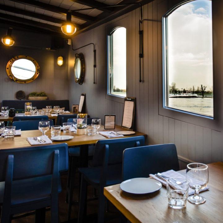 Schip verbouwd tot restaurant, gedekte tafels aan boord