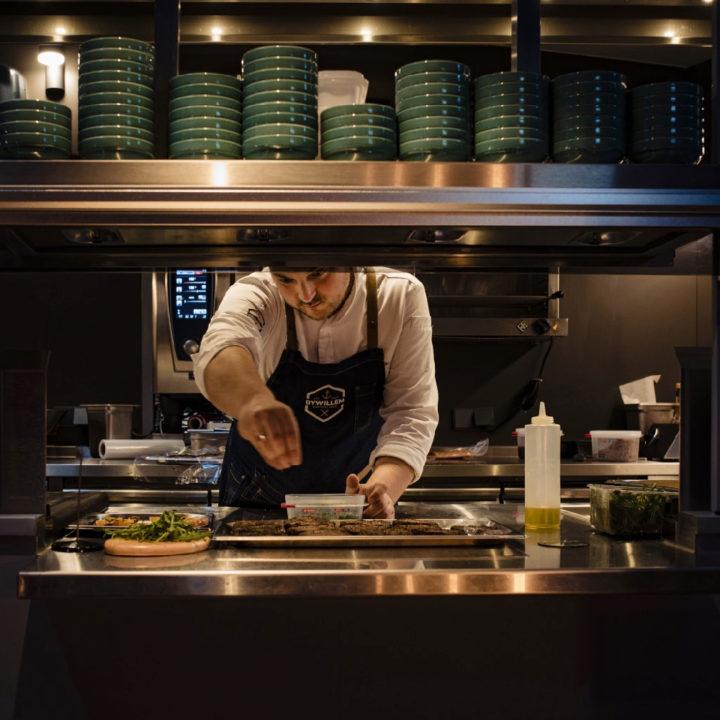 Open keuken waarin kok kruiden op het vlees strooit.