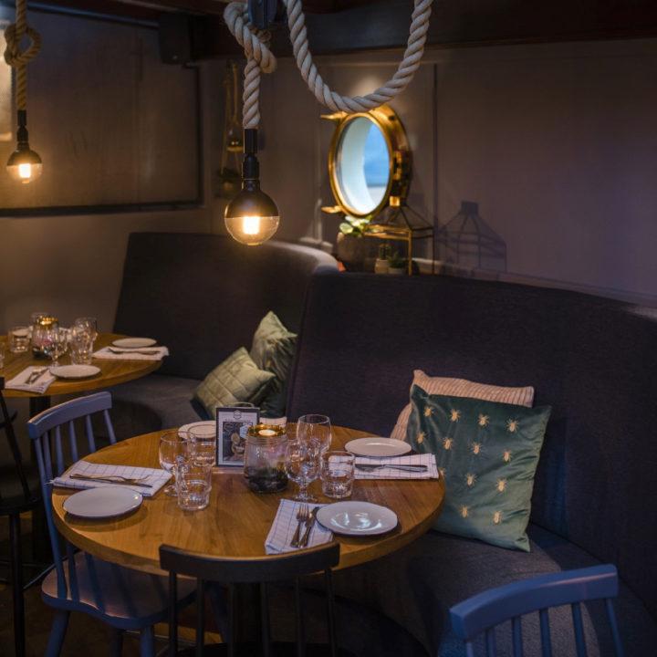 Gedekte tafel in een restaurant, met sfeerverlichting. Langs de muur een blauw fluwelen bank met kussens.