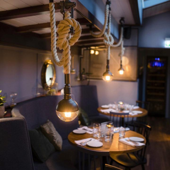 Gedekte tafels in een restaurant, verlicht door touwlampen