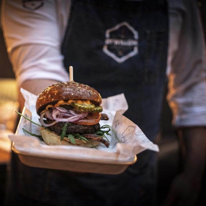 Een close up van een hamburger, in de hand gehouden door de kok
