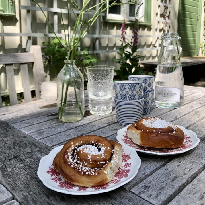 Kaneelbroodjes met glazen water op tafel in de tuin