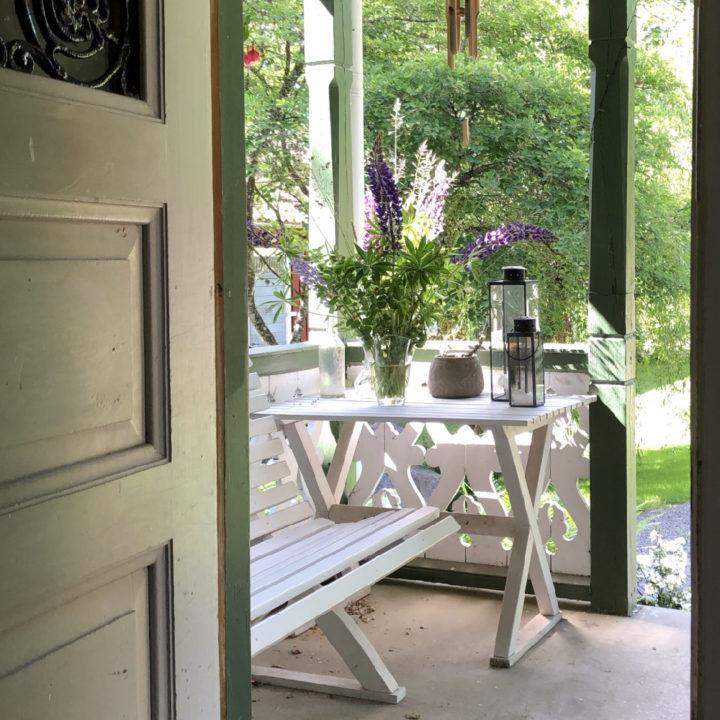 Wit bankje en wit tafeltje op de veranda
