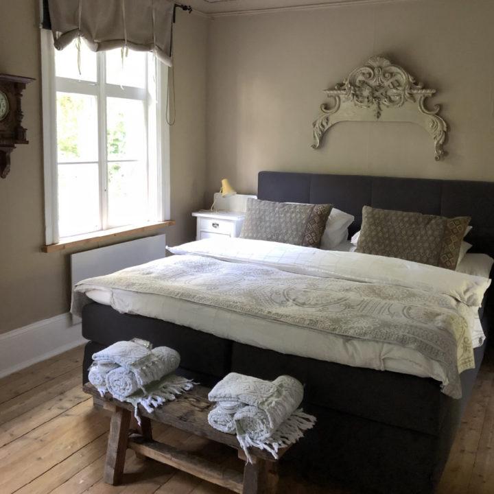 Tweepersoons bed met houten bankje met handdoeken